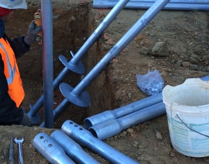 ECP helical piers being installed to raise new foundation slab